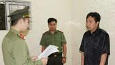 Tống đạt quyết định khởi tố bị can đối với Nguyễn Minh Cầm. Ảnh Công an Hà Tĩnh cung cấp