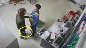 Đối tượng cầm dao khống chế nhân viên cửa hàng xăng dầu. Ảnh cắt từ clip