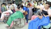 Các tình nguyện viên cắt tóc cho bệnh nhân