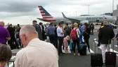Hành khách tập trung trên đường băng sau khi được sơ tán khỏi máy bay ở sân bay Manchester, Anh, ngày 5-7-2017. Ảnh: AP