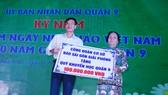 Ông Phạm Trường, Phó Tổng Biên tập Báo  Sài Gòn Giải Phóng, trao bảng tượng trưng ủng hộ Quỹ Khuyến học Quận 9 (TPHCM) 100 triệu đồng. Ảnh: TRỌNG NGHI
