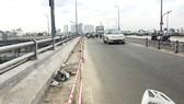 Phần lề đường dành cho người đi bộ trên cầu Nguyễn Tri Phương đang bị  phá bỏ để mở rộng lòng đường, người đi bộ không còn lối đi qua cầu