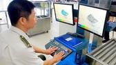 Nhân viên an ninh kiểm tra hành lý qua máy soi  tại sân bay Nội Bài