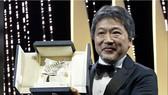 Đạo diễn Hirokazu Kore-eda và Cành cọ vàng danh giá. Ảnh: REUTERS