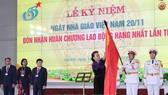 Chủ tịch Quốc hội Nguyễn Thị Kim Ngân gắn Huân chương Lao động hạng Nhất lần thứ hai lên lá cờ truyền thống của Học viện Tài chính. Ảnh: TTXVN