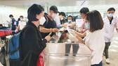 Khách từ Hàn Quốc thực hiện tờ khai y tế tại sân bay Tân Sơn Nhất rạng sáng 24-2. Ảnh: THÀNH SƠN