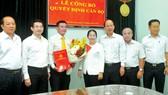 Phó Bí thư Thành ủy TPHCM Võ Thị Dung trao quyết định  và tặng hoa chúc mừng đồng chí Lê Kim Hiếu. Ảnh: CAO THĂNG