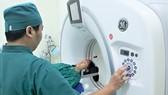 Kỹ thuật viên khu Khám bệnh chất lượng cao, Bệnh viện Quân Dân y miền Đông thao tác chụp ảnh cho bệnh nhân bằng máy MSCT - 128 lát. Ảnh: HOÀNG HÙNG