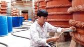 Kiểm tra chất lượng nước mắm trong quá trình rút kéo nước mắm bên trong nhà thùng tại Phú Quốc. Ảnh: NGỌC CHÁNH