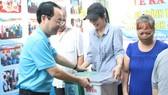 Bí thư Quận ủy quận 5 Nguyễn Văn Hiếu tặng thùng rác cho các hộ gia đình  tại lễ ra mắt hẻm xanh - sạch - văn minh  ở phường 1, quận 5. Ảnh: MAI HOA