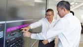Tổng Giám đốc EVNHCMC Nguyễn Văn Thanh (bìa trái) đang báo cáo về hệ thống điều khiển từ xa tại Trung tâm Điều độ hệ thống điện TPHCM với Tổng Giám đốc EVN Trần Đình Nhân