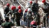 Lực lượng tìm kiếm và cứu hộ mang thi thể từ một đống đổ nát ở TP Ganja - Azerbaijan hôm 11-10. Ảnh: REUTERS