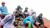 Lực lượng chức năng giúp người dân ở xã Thịnh Lộc (huyện Lộc Hà, tỉnh Hà Tĩnh) lợp lại mái nhà sau mưa bão. Ảnh: DƯƠNG QUANG