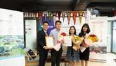 Nguyễn Duy An (thứ hai từ trái qua) cùng mẹ  và đại diện đơn vị trao học bổng