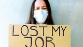 Một người lao động thất nghiệp ở Mỹ cầm tấm bìa ghi:  Tôi mất việc làm vì Covid-19