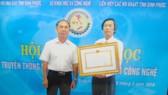 Ông Trần Văn Vân (phải) nhận Huân chương Lao động hạng hai tặng thưởng Sở KH-CN tỉnh Bình Phước