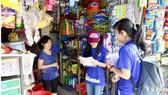Nhiều người dân tuyến đường Độc Lập (quận Tân Phú) đang được tình nguyện viên hướng dẫn  phân loại chất thải rắn tại nguồn