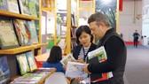 Một đối tác nước ngoài đang tìm hiểu các ấn phẩm của Việt Nam tại Hội sách Frankfurt 2019. Ảnh: HÒA LONG