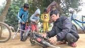 Anh Dũng sửa xe đạp cho các em học sinh ở bản Cồn
