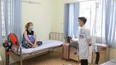 Bác sĩ Nguyễn Nhật Sang thăm hỏi người đang cách ly  tại khu cách ly quận Phú Nhuận. Ảnh: HOÀNG HÙNG