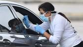 Nhân viên y tế kiểm tra tài xế tại London, Anh. Ảnh: Getty Images
