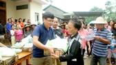 Đại diện Báo SGGP trao các phần quà đến người dân vùng lũ thuộc xã Hải Chánh, huyện Hải Lăng, Quảng Trị