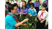 Trần Công Bình- Chuyên gia quyền trẻ em của UNICEF tại Việt Nam trao tặng cây xanh cho các em đội viên, học sinh. Ảnh: VOH