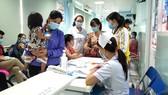 Phụ huynh bồng bế trẻ chờ thăm khám  tại Khoa Hô hấp Bệnh viện Nhi đồng 1 sáng 27-10