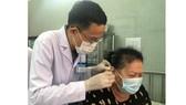 ThS-BS Nguyễn Văn Đàn thực hiện phương pháp nhĩ châm  cho bệnh nhân bị nhức mỏi. Ảnh: MINH NAM