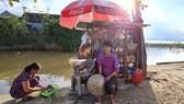Chị Lê Thị Trang bên quán tạp hóa nhỏ ven bờ kênh. Ảnh: MINH PHONG