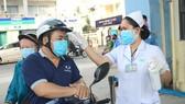 Người dân đến thăm khám tại Bệnh viện Da liễu TPHCM đều được đo thân nhiệt ngay từ cổng bệnh viện
