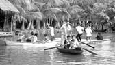 Du khách chèo xuồng vui chơi ở Làng du lịch Mỹ Khánh
