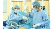 Bác sĩ Robert Riche và bác sĩ Hồ Nguyên Tiến trực tiếp thực hiện ca mổ nội soi điều trị cho bệnh nhân sa tạng chậu phức tạp