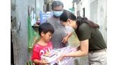 Đại diện Báo SGGP trao tặng máy tính bảng và tập vở mới cho bé Nguyễn Anh Tấn, con anh Nguyễn Văn Bình (quận Gò Vấp)