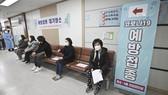 Người dân tuân thủ giãn cách chờ tiêm vaccine COVID-19 tại Seoul. Ảnh: AP
