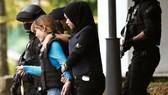 Đoàn Thị Hương (áo xanh) mặc áo chống đạn và được áp tải khỏi tòa hôm 13-4. Ảnh: Reuters.
