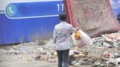 Vô tư vứt rác vào một bãi rác tự phát   Ảnh: THÀNH TRÍ
