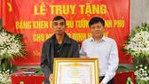 Phó Tổng Giám đốc Thông tấn xã Việt Nam Đinh Đăng Quang thừa ủy quyền của Thủ tướng Chính phủ trao Bằng khen của Thủ tướng Chính phủ cho gia đình cố Nhà báo Đinh Hữu Dư. Ảnh: TTXVN
