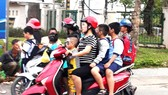 Phụ huynh không đội nón bảo hiểm cho con khi chở con đi đường