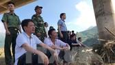 Các thành viên đoàn công tác theo dõi công tác tìm kiếm phóng viên Đinh Hữu Dư. Ảnh: Minh Đức/TTXVN