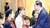 Chủ tịch nước Trần Đại Quang tặng quà các trẻ em có hoàn cảnh đặc biệt. Ảnh: TTXVN