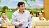 Bộ trưởng Bộ KH-ĐT Nguyễn Chí Dũng trình bày báo cáo về kinh tế - xã hội. Ảnh: TTXVN