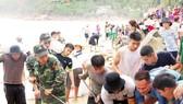 Lực lượng biên phòng, dân quân tự vệ và người dân nỗ lực sửa chữa kè biển xã Nhơn Hải, Bình Định. Ảnh: NGỌC OAI