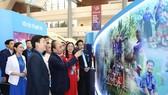 """Thủ tướng Nguyễn Xuân Phúc với các đại biểu tham quan Triển lãm """"Tôi yêu Tổ quốc tôi"""" tại Đại hội. Ảnh: TTXVN"""