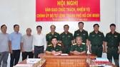 Thiếu tướng Nguyễn Minh Hoàng (thứ 4 từ bên phải sang) và các đại biểu chứng kiến Thiếu tướng Ngô Tuấn Nghĩa và Đại tá Phan Văn Xựng ký biên bản bàn giao. Ảnh: hcmcpv