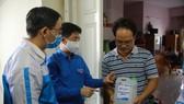Tặng dung dịch khử khuẩn cho cư dân chung cư Lê Thành (phường Bình Trị Đông A, quận Bình Tân). Ảnh: PHẠM ĐẠT - Tuổi Trẻ Online