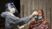 Nhân viên y tế lấy mẫu dịch xét nghiệm Covid-19 cho người dân tại New Delhi, Ấn Độ ngày 7-5. Ảnh: THX/TTXVN