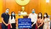 Bác sĩ Trần Quốc Khánh cùng đại diện của Thái Hà Books trao tặng số tiền 160 triệu đồng từ chương trình đấu giá sách ủng hộ Quỹ vaccine phòng Covid-19