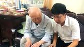 Ông Vĩnh Mẫn lật từng tấm ảnh kỷ niệm và kể về cuộc đời hoạt động cách mạng của mình với PV Báo SGGP