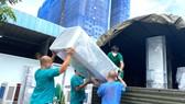 Nhân viên y tế Trung tâm Hồi sức Covid-19 do BV Bạch Mai quản lý đang vận chuyển đồ đạc trở về Hà Nội